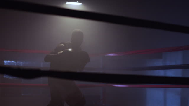 A boxer practices techniques beneath a light in the middle of a boxing ring.