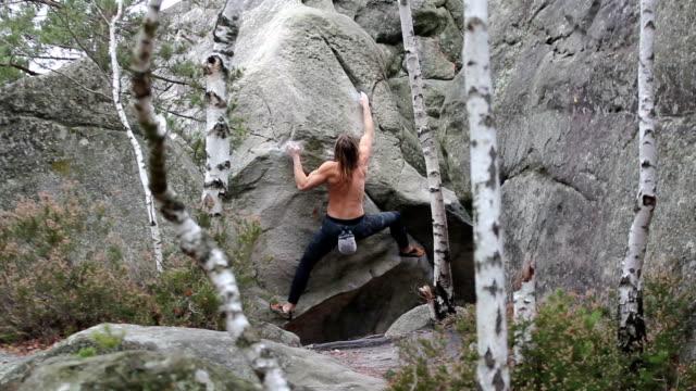 stockvideo's en b-roll-footage met muscular young man climbing a boulder in fontainebleau area - vrij klimmen