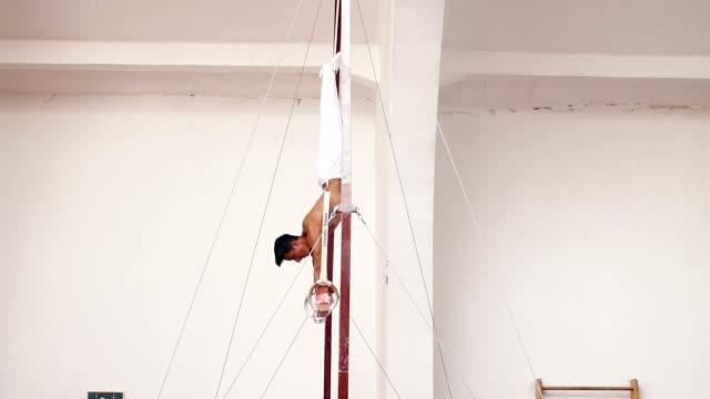 Muskulösen jungen Mann auf Gymnastik Ringen