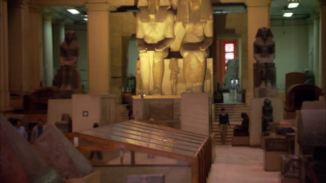 museum patrons walk around ancient egyptian artifacts. - arte dell'antichità video stock e b–roll