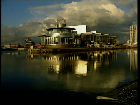 LS Lowry arts centre to be opened ENGLAND Manchester Salford EXT Manchester ship canal Ship canal PAN LR The Lowry art centre on edge of docks The...