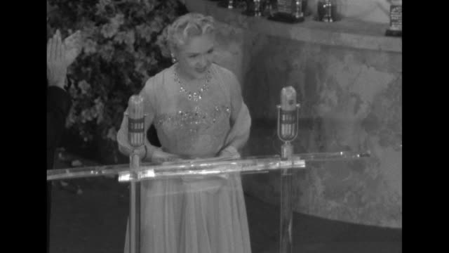 vídeos de stock e filmes b-roll de vo music as pan down birthday cake statue topped by giant oscar statue with smaller lighted oscars representing candles to actress mary pickford... - bob hope comediante