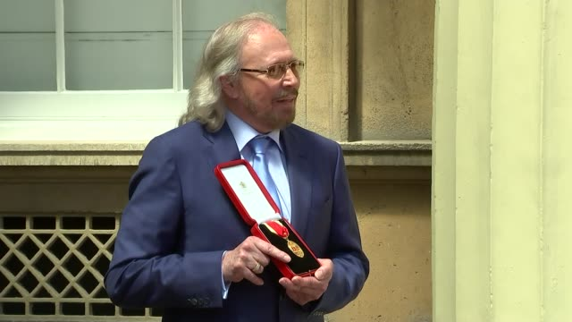 barry gibb interview on receiving knighthood; england: london: buckingham palace: ext various shots barry gibb photocall with cbe medal / with family - the bee gees bildbanksvideor och videomaterial från bakom kulisserna
