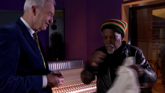 billy ocean interview england london int billy ocean showing photos to channel 4 news reporter jon snow and chatting sot / ocean showing outfit he... - jon snow journalist stock-videos und b-roll-filmmaterial