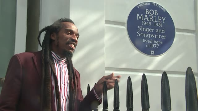 blue plaque unveiled for bob marley in chelsea; england: london: chelsea: ext sun silhouette seen through clouds benjamin zephaniah singing next to... - ボブ・マーリー点の映像素材/bロール