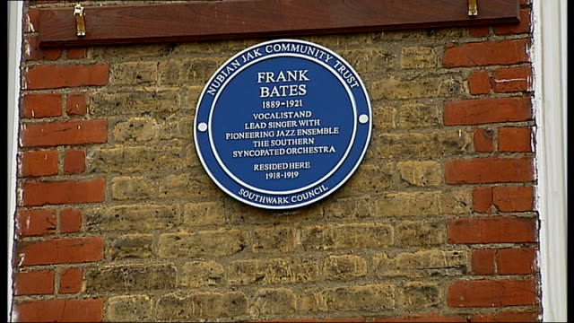vídeos de stock e filmes b-roll de blue plaque unveiled in memory of jazz musician frank bates; england: london: peckham rye: hichisson road: ext blue heritage plaque in memory of... - peckham