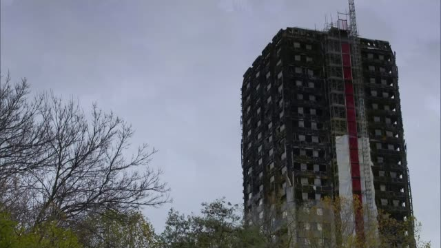 brit awards 2018 stormzy accuses theresa may of failing victims of grenfell tower fire firedestroyed grenfell tower with leaves on tree in foreground... - stormzy stock videos and b-roll footage