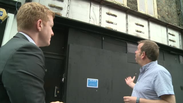 campaign to save music venues in london; various shots reporter along with jeff horton looking at framed photographs of performers at club jeff... - street name sign stock-videos und b-roll-filmmaterial