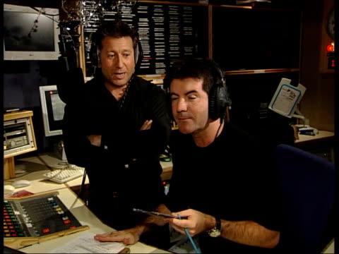 christmas no 1 england london dj neil fox and simon cowell in radio studio as cowell conducting interview with gary jules sot - 2003 bildbanksvideor och videomaterial från bakom kulisserna