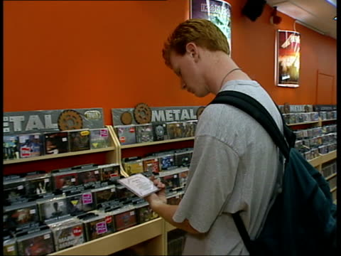 napster website tower records bv man looking at cd in metal section of record shop ls cd held zoom in with picture breaking up and reforming to show... - tower records stock videos & royalty-free footage