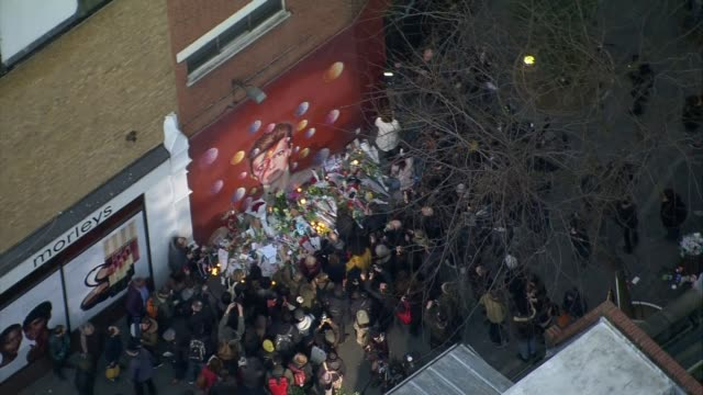 david bowie dies aged 69 england london brixton crowd gathered in front of david bowie [ziggy stardust] mural with memorial floral tributes and... - 仮設追悼施設点の映像素材/bロール