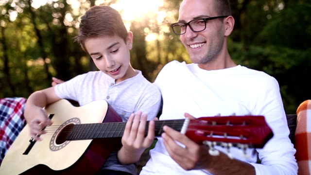 music family - plucking an instrument stock videos and b-roll footage