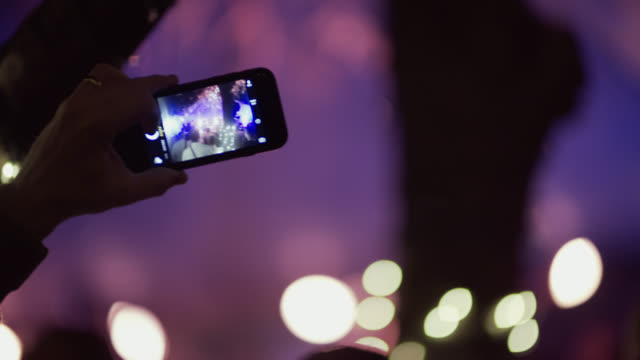 Music fan holds up smartphone to snap a photo of band at outdoor music festival