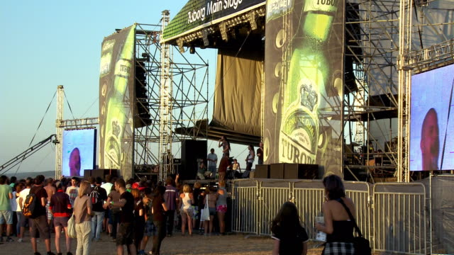 Music fans gather near the main stage as a rock band performs at an outdoor festival.