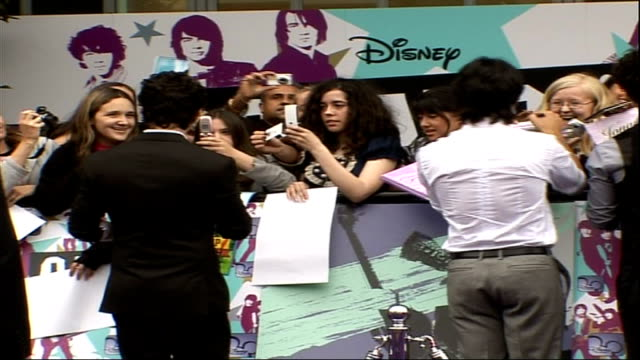vídeos y material grabado en eventos de stock de 'camp rock' film premiere; young female fans / back view of the jonas brothers signing autographs / demi lovato posing / jonas brothers along / demi... - autografiar