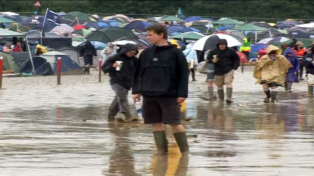 glastonbury festival: rain turns site to mud; festival goer standing in mud as others squelch past behind more festival goers along through mud... - festival goer stock videos & royalty-free footage