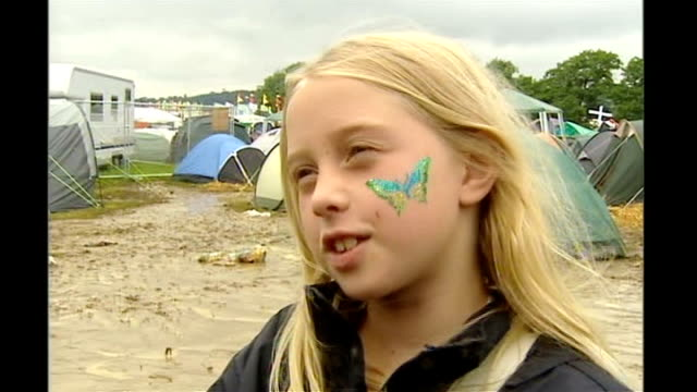glastonbury festival: rain turns site to mud; vox pops sot - soil stock videos & royalty-free footage
