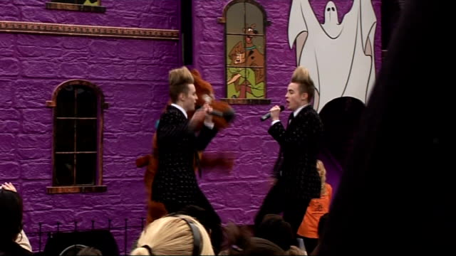 jedward perform at battersea dogs cats home for scoobydoo launch jedward performing song 'under pressure ' on stage with scooby doo character dancing... - jedward stock videos and b-roll footage