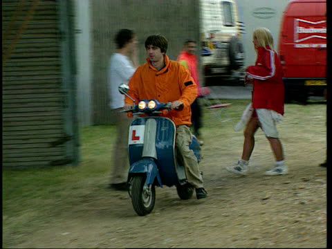 liam gallagher absent from 'oasis' us tour; tx 9.8.1996 hertfordshire: knebworth: sequence noel gallagher along on motor scooter around with balloon... - オアシス点の映像素材/bロール