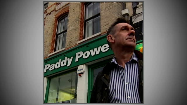 morrissey's autobiography published; east london: graphicised shot reporter standing outside paddy power shop - biografia video stock e b–roll