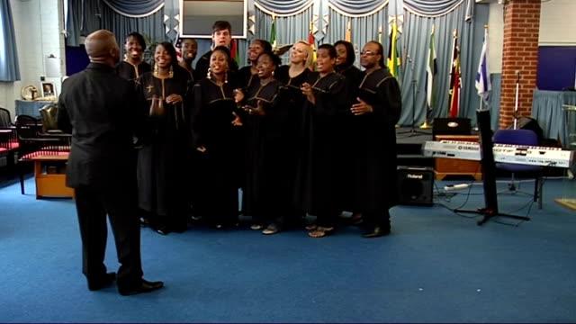 london community gospel choir performing; england: london: int **music heard sot** wide shot of the london community gospel choir singing song 'abide... - ロンドン コミュニティ ゴスペル クワイア点の映像素材/bロール