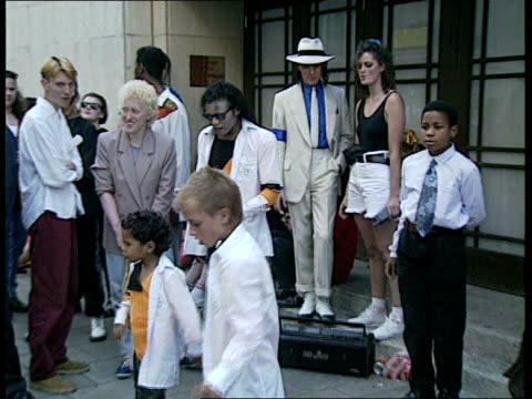 michael jackson arrives in uk and visits children's hospital; england: london: park lane: ext park lane jackson fans, lookalikes and dressalikes... - dorchester hotel stock videos & royalty-free footage