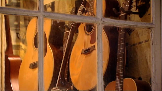 music heritage of denmark street ext traffic on street guitars displayed in shop window 12 bar club music venue hanks guitar store guitars and... - guitar stock videos & royalty-free footage