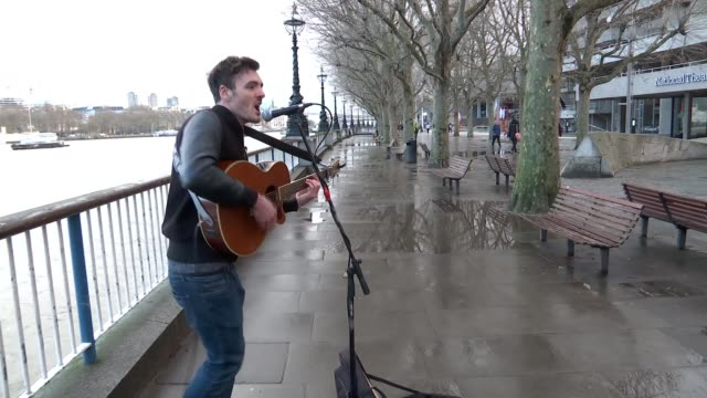 new app to tip buskers england london ext money being placed in busker's guitar case various shots dawson playing guitar and singing watched by... - plucking an instrument stock videos and b-roll footage