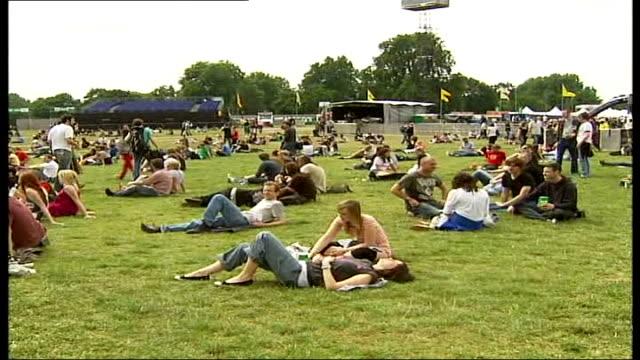 stockvideo's en b-roll-footage met wireless festival in hyde park; england: london: hyde park: ext o2 wireless festival main stage people relaxing on the grass roadies tuning guitars... - festivalganger