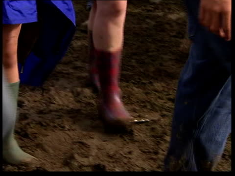reading festival arrivals england berkshire reading ext various shots of legs of festivalgoers along through mud group of people sitting in mud... - reading and leeds festivals stock videos & royalty-free footage