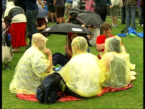 rise music festival festivalgoers sheltering under umbrellas and raincoats in rain as band heard performing on stage sot/ festivalgoears shelter... - waterproof clothing stock videos & royalty-free footage