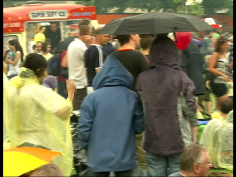 rise music festival festivalgoers sheltering under umbrellas and raincoats as band heard performing on stage sot - waterproof clothing stock videos & royalty-free footage