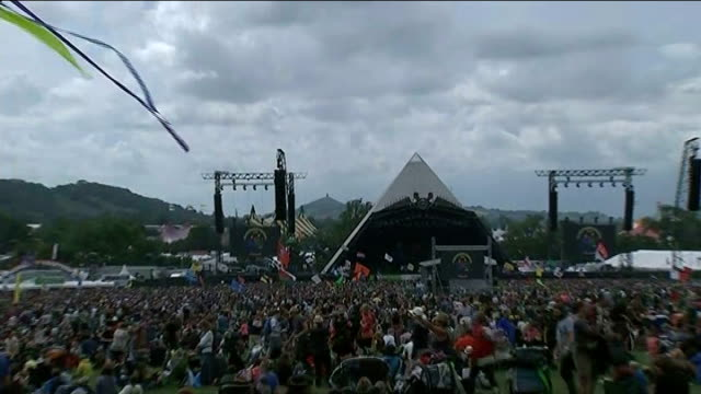 storms interrupt glastonbury festival; long shot of pyramid stage under dark clouds and fans gathered in front - glastonbury tor in distance - glastonbury tor stock videos & royalty-free footage