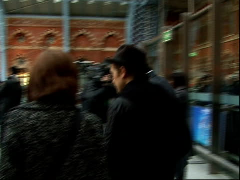stockvideo's en b-roll-footage met take that at st pancras international station mark owen waving to fans through screen and away / various of 'take that the circus' promotional posters - jongensband