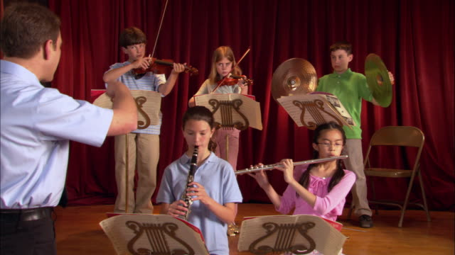 vídeos de stock e filmes b-roll de music teacher conducting children during band practice / ending piece / students taking a bow / los angeles, california - criança de escola primária