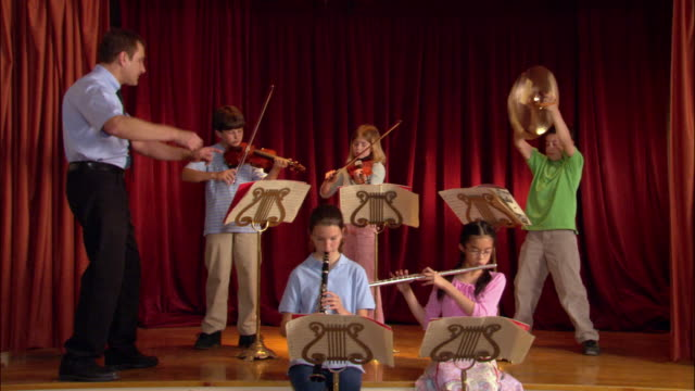 Music teacher conducting children during band practice / Los Angeles, California