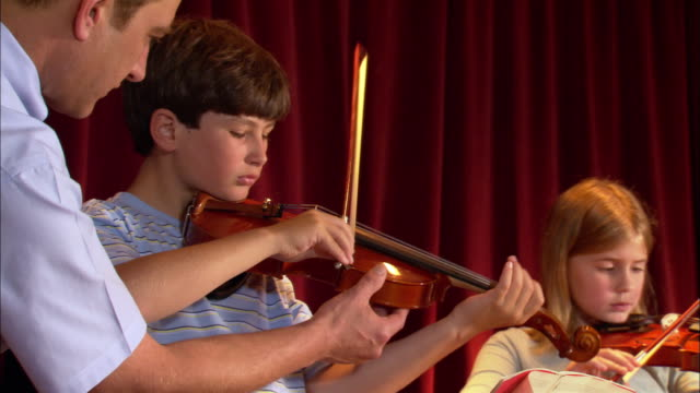Music teacher correcting boy's technique on violin in music class / looking over shoulder of girl playing violin / correcting technique / Los Angeles, California