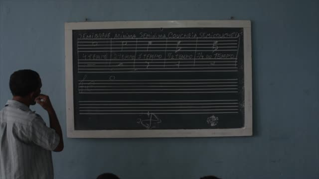 vidéos et rushes de music teacher in front of the blackboard imparts lessons of music theory. - professor