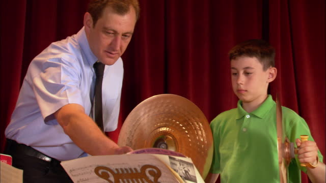 music teacher instructing boy playing cymbals during band practice / los angeles, california - cymbal stock videos and b-roll footage