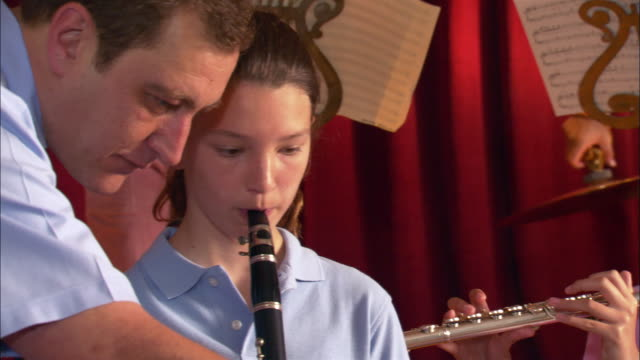Music teacher instructing girl playing clarinet during band practice / Los Angeles, California
