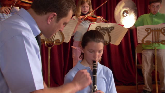 music teacher instructing girl playing clarinet during band practice / turning page of score for girl / los angeles, california - conductor stock videos and b-roll footage