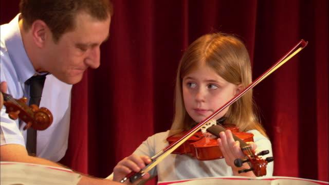 vídeos de stock, filmes e b-roll de music teacher instructing girl playing violin / los angeles, california - 8 9 anos