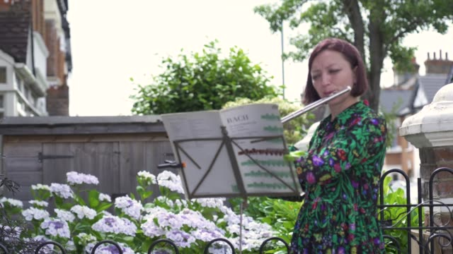 music teacher zoe purdiewood performs a classical music concert for 79 year old barbara layton – retired maths teacher outside her home in east... - musician stock videos & royalty-free footage