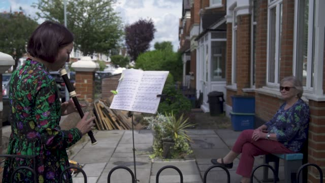 music teacher zoe purdie-wood performs a classical music concert for 79 year old barbara layton – retired maths teacher, outside her home in east... - performance stock videos & royalty-free footage