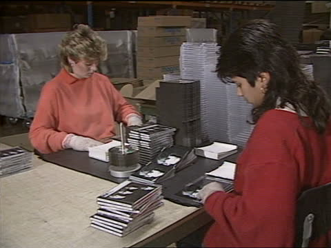the beatles on cd; int various shots of factory labelling and packing the beatles compact disc; - compact disc stock videos & royalty-free footage