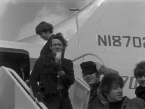 the hollies leave for usa; england: london: lap : int people towards with 'the hollies' ext wave from steps - windy neg 16mm brenards - music stock videos & royalty-free footage