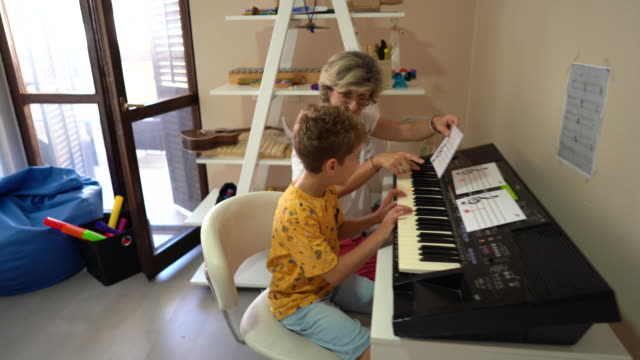 music therapist and boy playing synthesizer at rehabilitation center - invisible disability stock videos & royalty-free footage