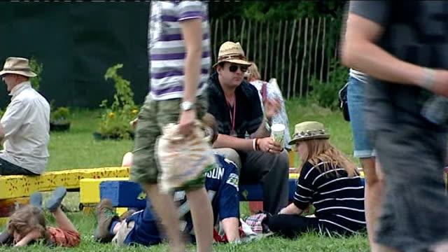 vídeos de stock, filmes e b-roll de thousand arrive for the glastonbury festival england somerset glastonbury ext people along at glastonbury festival / tents flags blowing in wind /... - stop placa em inglês