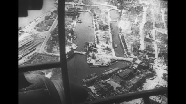 music throughout] vs aerials of rotterdam after german bombing attack; plane struts, windows, pilot's foot, and propeller in foreground; below are... - world war ii stock videos & royalty-free footage