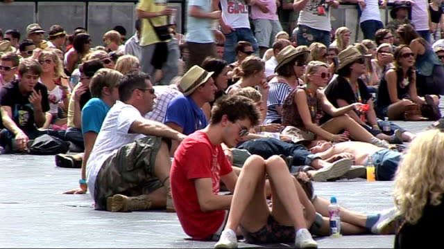 vidéos et rushes de festival 2010: day two; england: essex: chelmsford: ext general views posters / crowds of festival-goers relaxing / stage / track forward along... - audience de festival